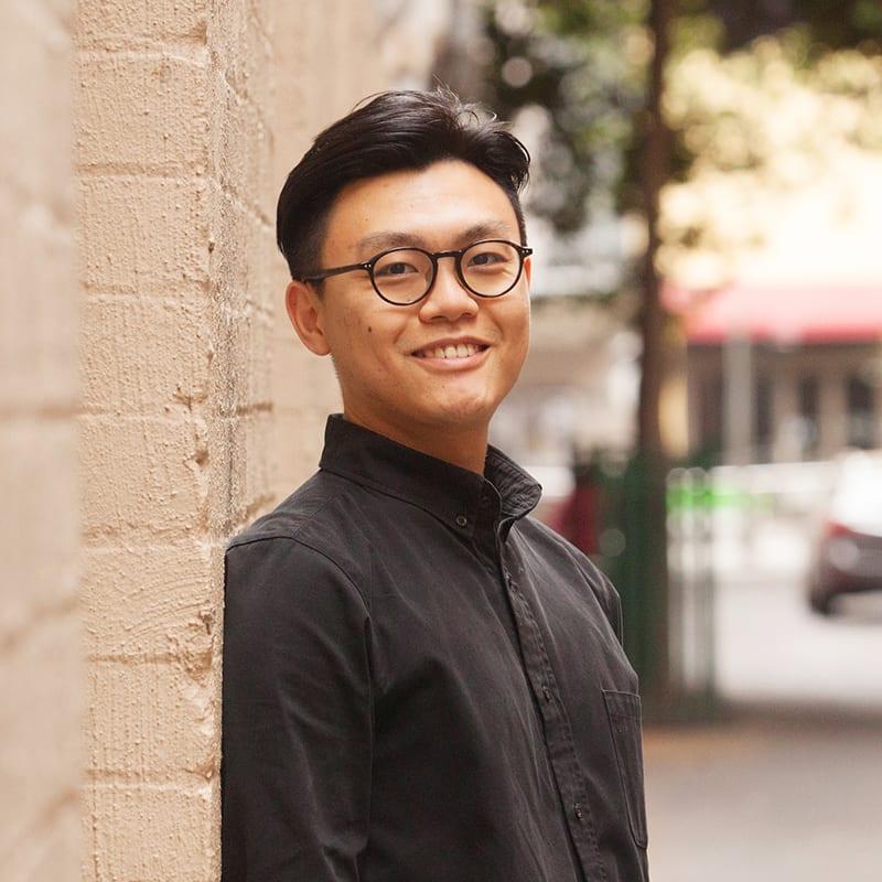 Xujie Fang standing in city laneway