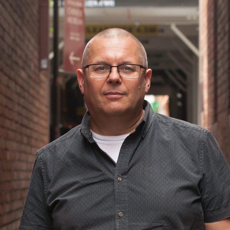 Andrew Partos standing in city laneway