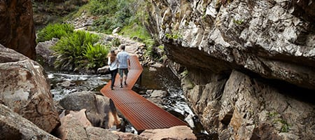 A couple walking up a corten steel walkway across a waterway at MacKenzie Falls